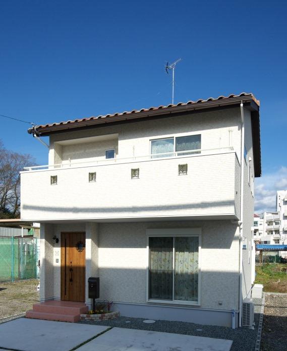 明和住宅【子育て、収納力、間取り】外観 白い外壁とオレンジの瓦屋根、木調の玄関ドアで南欧地方の住宅のイメージを実現した外観