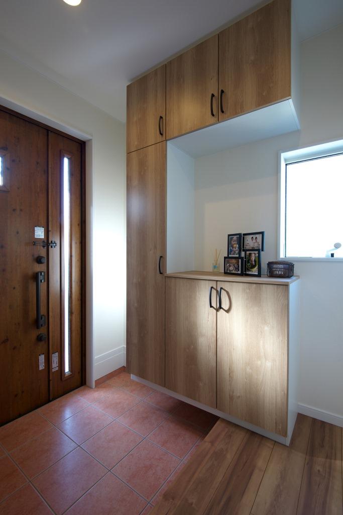 明和住宅【子育て、収納力、間取り】玄関ホール 大容量の下駄箱の他に、クローゼットタイプの土間収納も備えた。テラコッタ調のタイルは外階段へと続き、外観との統一感をもたらす
