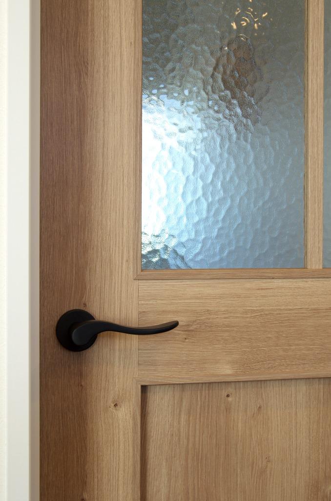 明和住宅【子育て、収納力、間取り】玄関とリビングを仕切るのは、奥さまチョイスのドア。模様ガラスからほんのり透けて見える様子もお気に入り