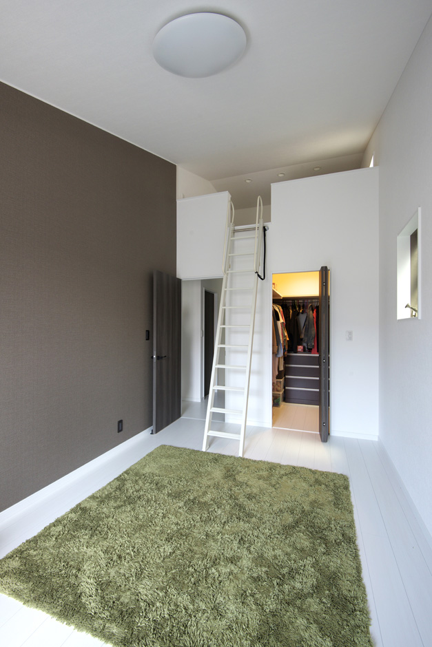 明和住宅【子育て、収納力、省エネ】寝室 太陽光発電パネルを乗せるために、勾配を付けた天井を活かして、寝室にはロフトを。その下のウォークインクローゼットも使いやすい