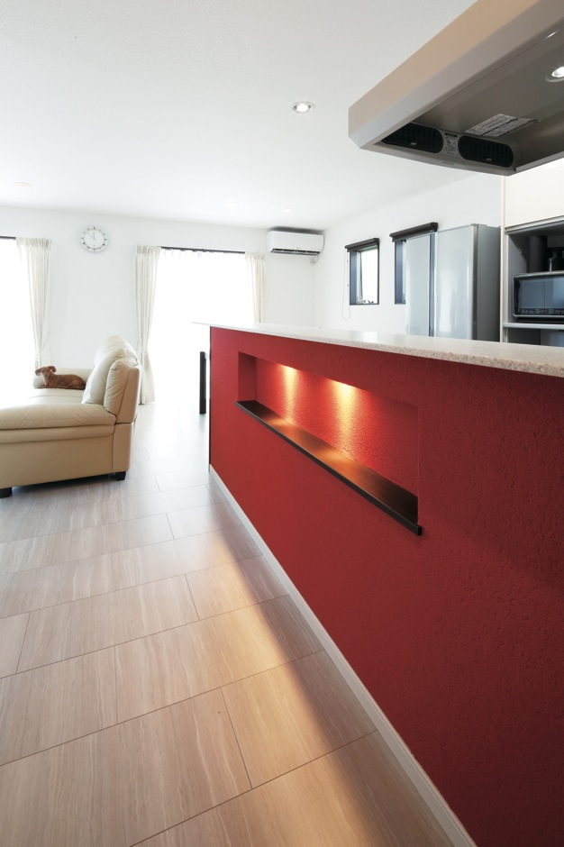 明和住宅【子育て、間取り、ペット】カウンターはビーズ入りの塗り壁と深みのある赤で、ラグジュアリー感を演出。天板も木ではなく、大理石調に