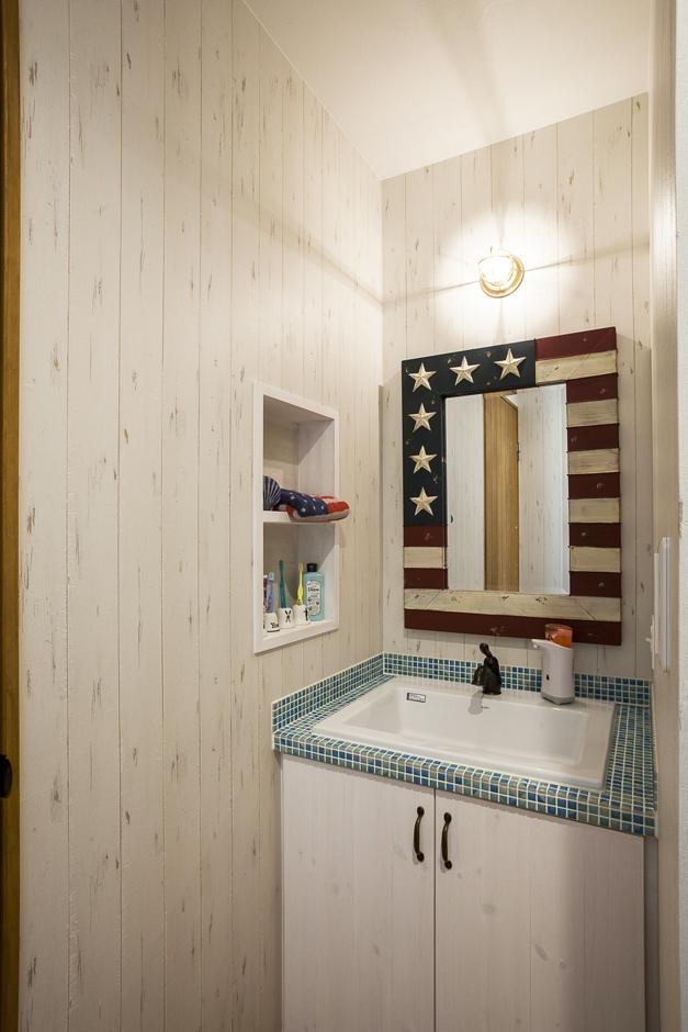 洗面所の鏡は奥様がお気に入りのショップで購入したもの。そのイメージに合わせてタイルや壁を選んだ