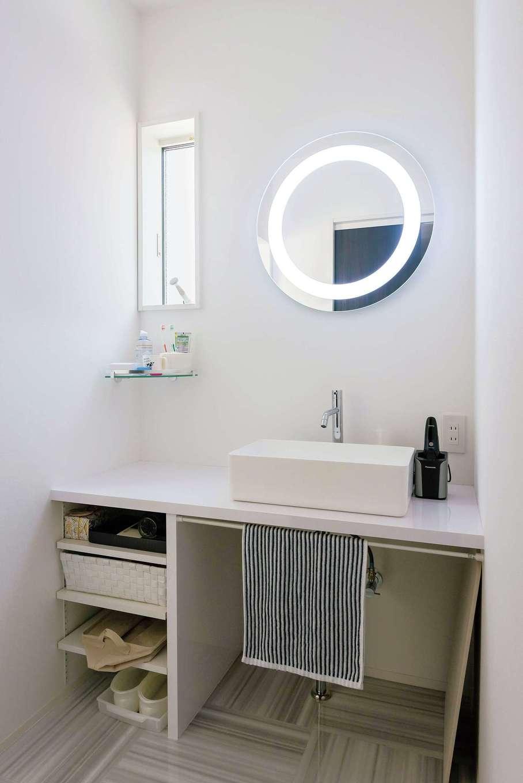 """洗面台の鏡は、照明が内蔵された""""女優ミラー""""。毎日の身支度が楽しくなる空間。スクエアのシンクと丸い鏡の組み合わせも絶妙。洗面台の下はオープンな収納スペースにして、スタイリッシュ感を強調している"""
