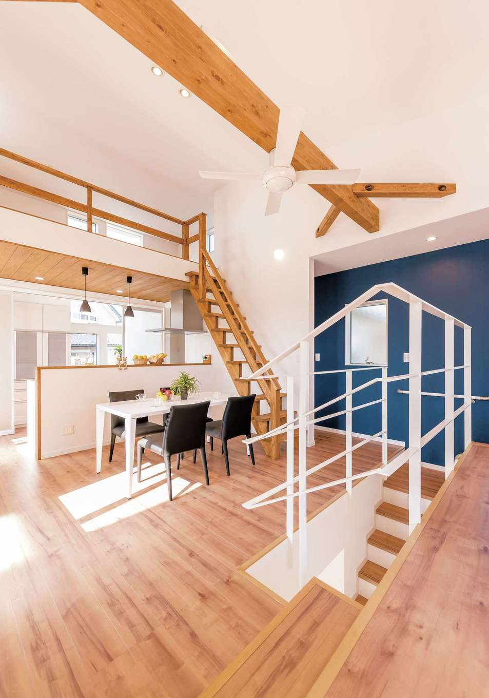 三和建設【デザイン住宅、子育て、間取り】階段からは左右どちらにも回れる動線を確保。ダイニングとリビングはスキップフロアで空間にアクセントを。キッチン上部にはロフトもあり、縦空間の広がりも感じる
