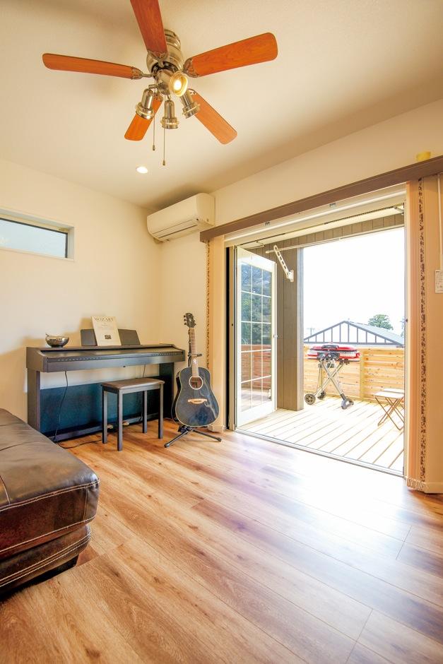 三和建設【子育て、趣味、スキップフロア】1階のウッドデッキへと続く洋室には、練習用の電子ピアノとギターが置かれている
