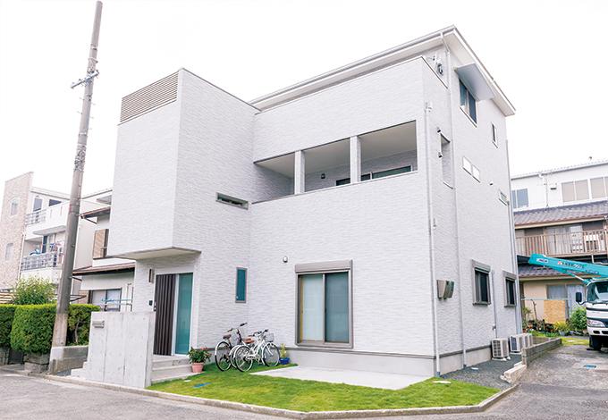 三和建設【収納力、二世帯住宅、屋上バルコニー】明るい白をチョイスした外観。玄関上部の横スリット窓やインナーバルコニーも表情を添える