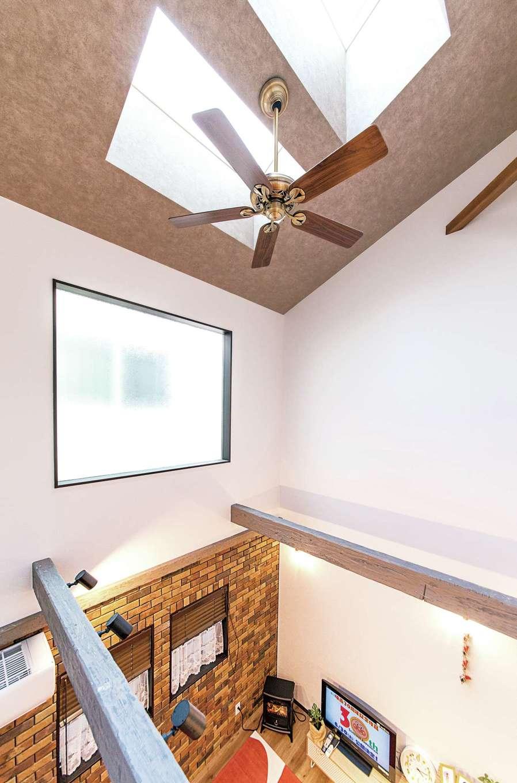 三和建設【子育て、収納力、自然素材】吹き抜けの壁の上部には大きな窓が。さらに天井にはトップライトを設け、採光は充分。天井のシーリングファンが家中の空気を循環させるので、冷暖房効率もアップ