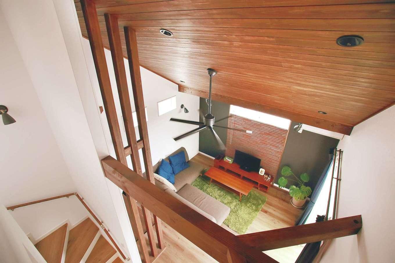 シーリングファンの回る勾配天井が理想。実現するためにリビングは2階に設けた。同色で整えた天井と梁で落ち着きのある空間を演出