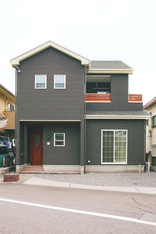 ダークカラーのラップサイディング調とバルコニーや玄関ドアの赤みがかった木調がマッチした外観。屋根の白いトリミングもアクセントに