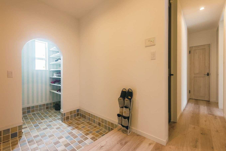 玄関ホールのシューズクローゼットも壁をアーチにしてかわいらしい雰囲気に。床のタイルで個性を演出