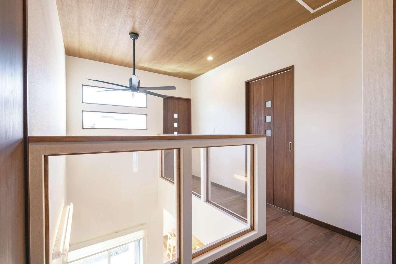 子どもの安全を考えた2階ホールの腰壁は、アクリル板で採光と見通しの良さを確保。床や建具に色を合わせた木枠がポイント。天井のクロスはご主人のセレクト。