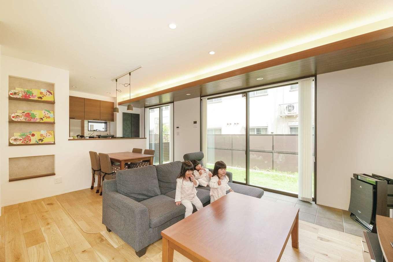キッチンからはリビングや庭が見渡せ、元気に遊ぶ子どもたちに目が届く。キッチンのサブウェイタイルや、間接照明と組み合わせた窓側の木目天井がインテリアのアクセントに