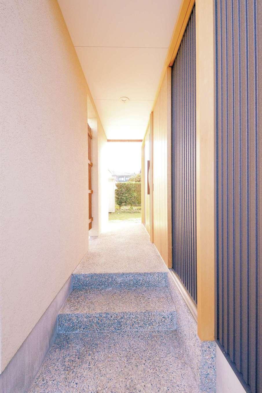 T-style 【収納力、自然素材、省エネ】東からの強風よけとデザイン性を兼ねた趣のあるアプローチ。洗い出しのステップと大きな玄関引き戸が高級感を演出