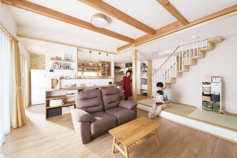 キッチンとリビングとの境はアミューズメントパーク好きの夫妻の思い出を飾る棚を設置。階段下の畳スペースにもほっこり