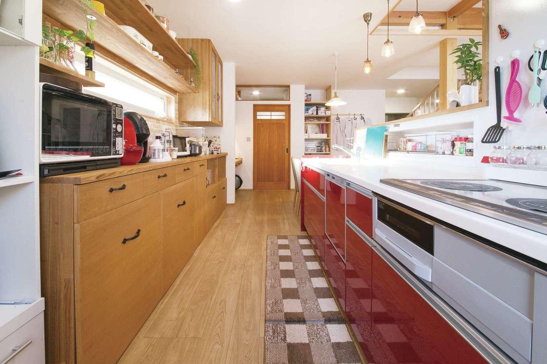閉ざされた空間だからこそ、遊び心を。キッチンパネルをレッドにして、気分をアップ。ゴミ箱も収納式で、すっきりとした空間に