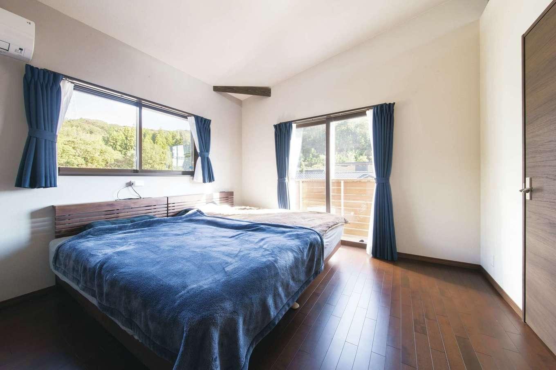 シックなデザインの寝室。丘の上の角地なので、窓を大きく取ってもプライバシーが守られる