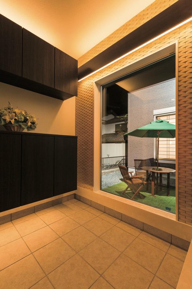 FIXの窓越しに視線が抜け、より開放的に感じる玄関ホール。タイル壁にバランス照明を設置し、光を上下に拡散させることで癒し効果をもたらす