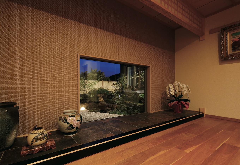 住宅工房 アリアンス【デザイン住宅、和風、高級住宅】玄関正面の窓越しに広がる坪庭の夜景は写真のよう。優美な空間でゲストをおもてなし