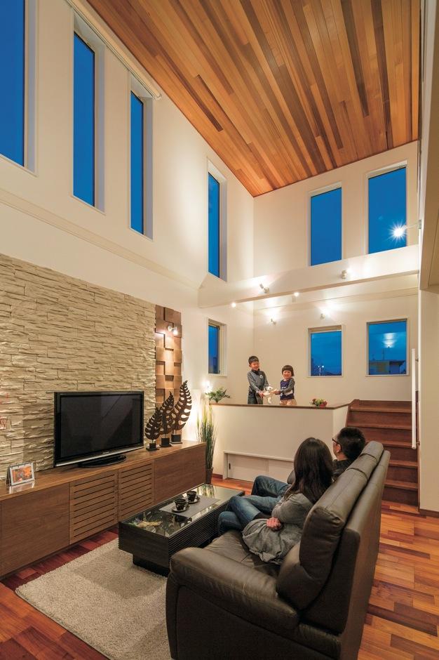 住宅工房 アリアンス【デザイン住宅、子育て、間取り】天井にも羽目板を張って高級感を出した吹抜けのリビング。ハイサイドサッシからの光が室内の奥まで届き、朝から夕方までずっと明るい。キッズスペースの子どもたちとソファでくつろぐ親との目線がほぼ同じ高さになるので、コミュニケーションをとりやすい