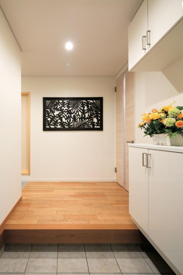 住宅工房 アリアンス【デザイン住宅、子育て、間取り】バリ製のウッドレリーフを引き立たせるべく、天井も壁もシューズクロークもすべて白で統一した玄関