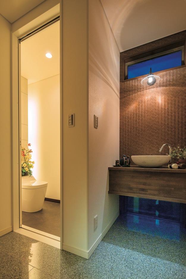 住宅工房 アリアンス【デザイン住宅、子育て、間取り】玄関ホールの一角に設けたサニタリー。トイレは『アリアンス』のリゾート館と同じデザイン。洗面コーナーはクロス、照明、陶器を厳選してバリ風に演出