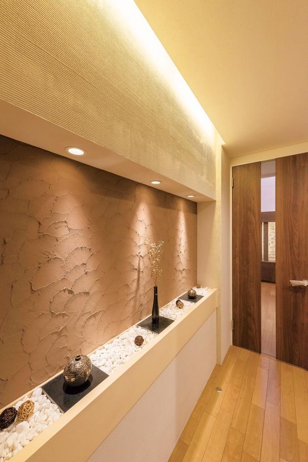 住宅工房 アリアンス【デザイン住宅、和風、間取り】玄関ホールは家の「顔」。現場監督の提案により、表情豊かな塗り壁と白い玉砂利を融合させ、和モダンな雰囲気に。間接照明のあて方ひとつにしてもセンスが光る