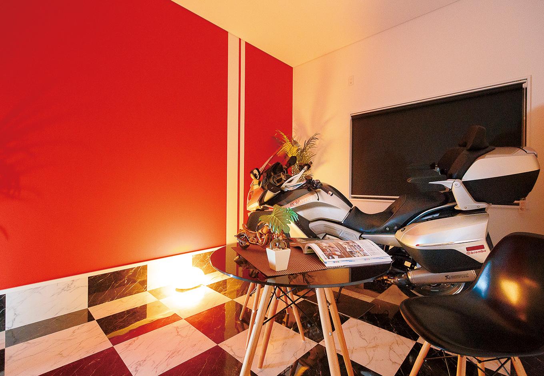 ご主人の夢を叶えたビルトインのバイクガレージは、1600ccのBMWが余裕で収まる7.2畳。ブラック&ホワイトのフロアタイルが高級感を演出。鮮やかな赤い壁と白のラインの組み合わせは前嶋社長のセンス。バイクがない時は、おうちカフェとしても使えそう