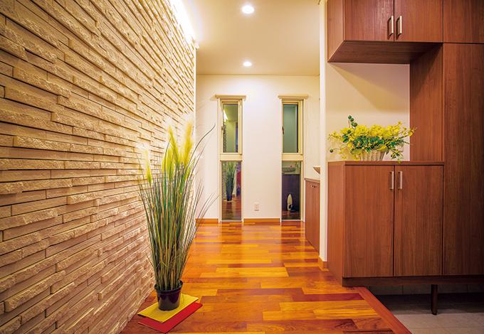 住宅工房 アリアンス【デザイン住宅、省エネ、インテリア】ゆった りとした玄関ホールはご夫妻のこだわり。ライトアップされた立体的な石壁に誰もが歓声を上げる