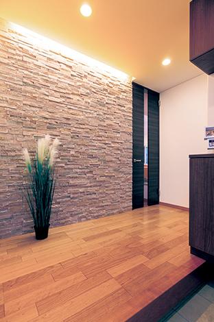 住宅工房 アリアンス【デザイン住宅、省エネ、間取り】凹凸のある石壁が上から照らされ、陰影が高級感を醸し出す玄関ホール