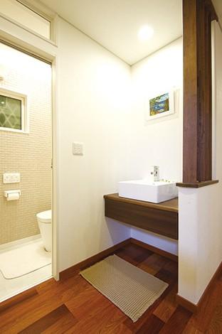住宅工房 アリアンス【デザイン住宅、子育て、間取り】洗面台はゲストが使うことを想定し、脱衣室とは別に用意。トイレとともにモダンなトーンでまとめられた