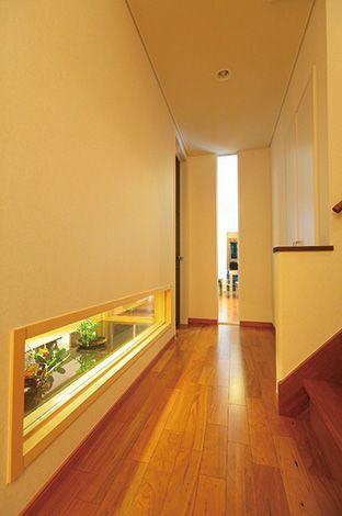 住宅工房 アリアンス【デザイン住宅、高級住宅、間取り】南北に長い敷地を考慮して、壁にスリット窓を入れ、視線を奥へと伸ばす工夫をした。和室の地窓からも光がこぼれる