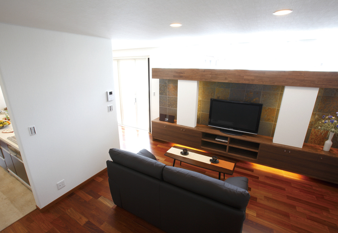 住宅工房 アリアンス【デザイン住宅、趣味、省エネ】家族の会話が弾むリビング。テレビステーション上部には鏡が貼られていて、窓からの光を壁や天井にバウンドさせている