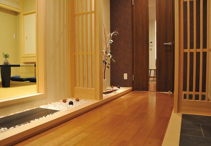 住宅工房 アリアンス【デザイン住宅、趣味、省エネ】玄関ホールはしっとりとした風情。玉砂利、踏み込み、竹格子などの和のエッセンスが空間に安らぎを与えている。通りからはこの部分だけが見え、客人の想像をふくらませる