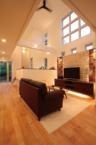 住宅工房 アリアンス【デザイン住宅、高級住宅、間取り】石貼りのテレビステーションが家族の団らんに上質なくつろぎを添える。9連の窓からは明るさと周囲の木々の緑。通り側を閉じることで、プライベート感が守られている