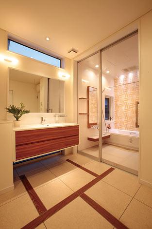 洗面脱衣室はひと休み用のソファが置けるほどの広さを確保。洗面台と浴室の雰囲気にあわせ、フロアにも手をかけた