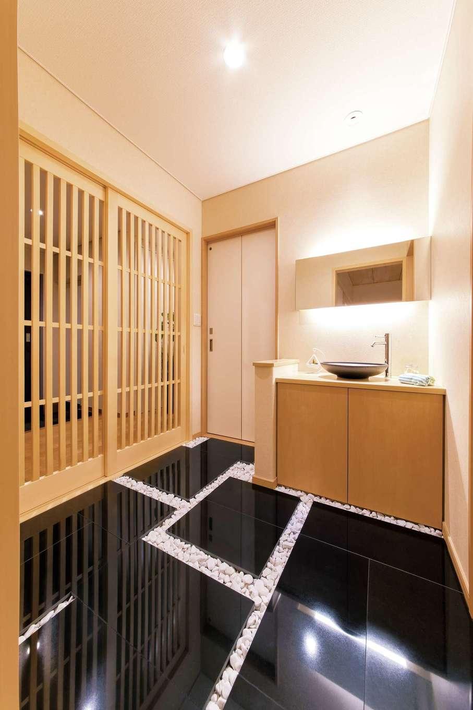 玄関から格子戸を開け、客間へとつながる動線に踏込みを採用。造作の洗面台と化粧室を配置し、ゲストを招く