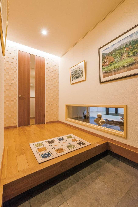 亡き父親が描いた思い出の絵画を玄関に飾ってホームギャラリーに。正面の壁に調湿効果にすぐれたエコカラットを貼り、すっきりとした空気を保つ