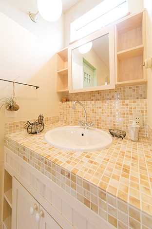 ホワイトとベージュのモザイクタイル。扉材はキッチンと同じ板を使用
