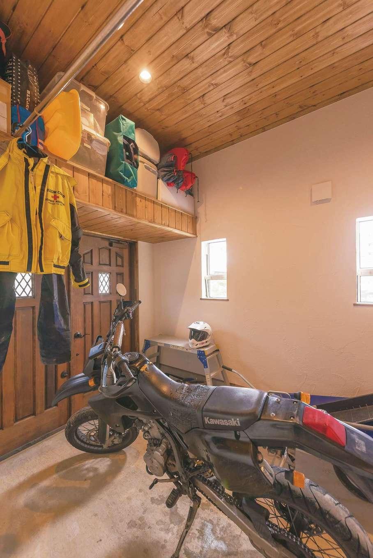 玄関からも出入りできるバイクガレージは男の隠れ家。収納スペースも充実させ、キャンプ用品などのアウトドアグッズもすっぽり入るので、奥さまも大助かり。木製の扉は観音開き