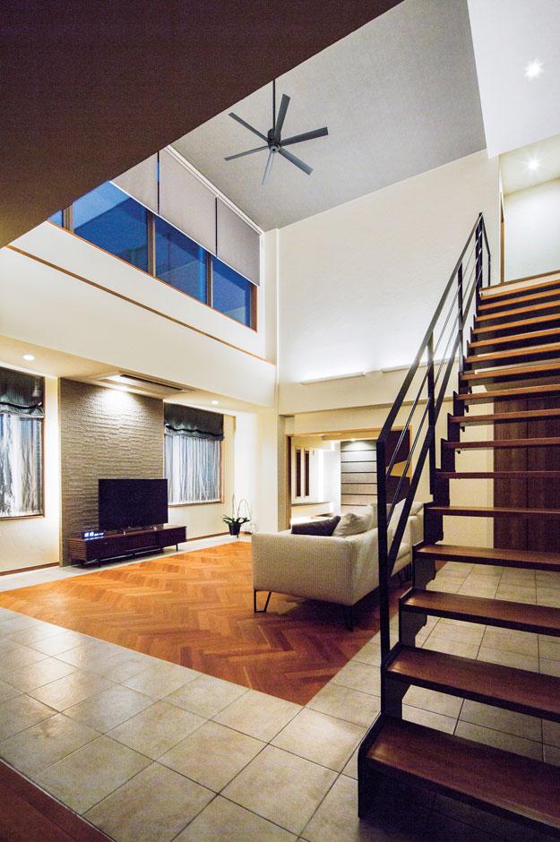 藤井建築事務所 -delphi-【デザイン住宅、建築家、鉄骨鉄筋コンクリート構造】吹き抜けの大空間をより広く見せるのは、スタイリッシュなスケルトン階段。タイルとアメリカンチェリー材のヘリンボーンの床の組み合わせはご主人の提案で。無垢材の部分には床暖房を設置