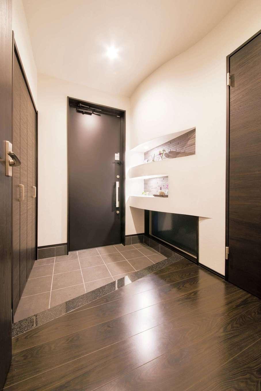 玄関の上り框には、キッチンカウンターと同じ天然の御影石を採用。アールを描いたニッチには、エコカラットを貼り、訪れる人を迎える空間を爽やかに保つ