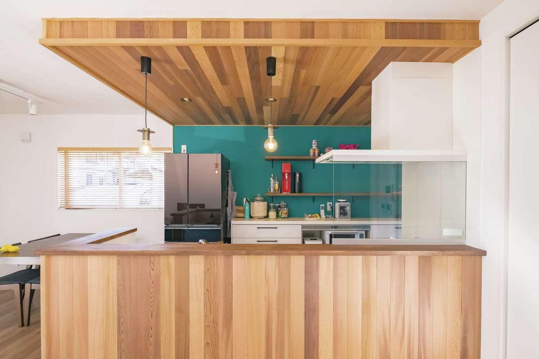 藤井建築事務所 -delphi-【デザイン住宅、間取り、建築家】ターコイズブルーの壁紙が映えるキッチン右奥にはパントリーとして使える収納を設置