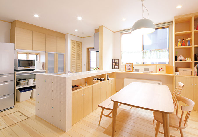 河原崎建設【デザイン住宅、子育て、自然素材】奥さまお気に入りのタイル貼りのキッチン。カウンターや本棚も雰囲気に合わせて造作された。冬場が苦手というご夫婦は、建物をじんわりあたためる蓄熱暖房を採用