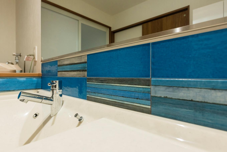 洗面所にはEさんチョイスの色鮮やかなブルーのタイルを使用。