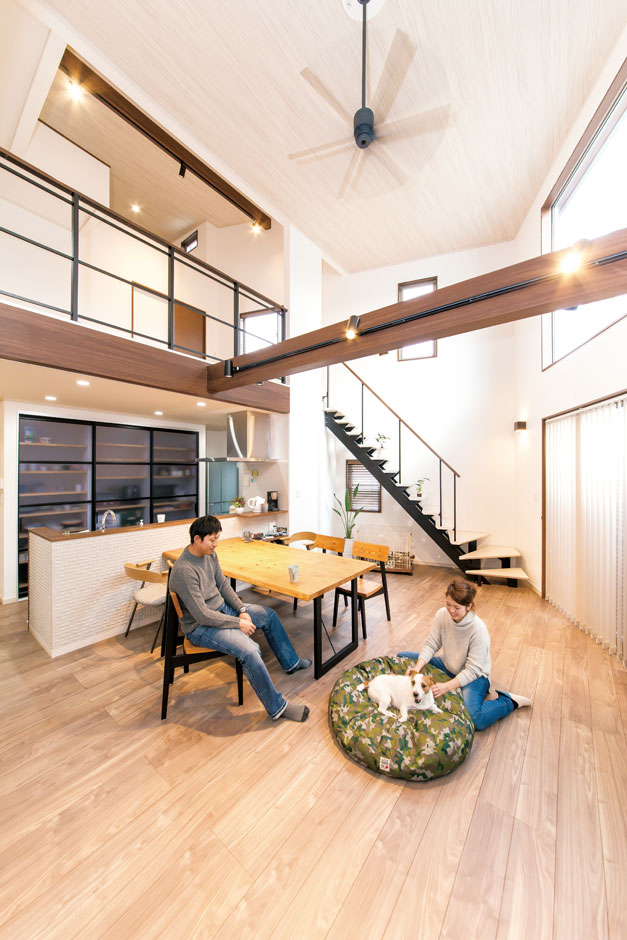 サンワ開発【デザイン住宅、収納力、間取り】吹き抜けのリビング。南側に配した大きな窓が暖かな日差しを程よく取り込む。またキッチンの背面を全面収納にすることでスッキリ見せた