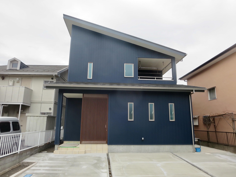 紺のガルバリウムにウッドが映える外観。玄関前の格子は、正面を通る道路から家の中が見えないようにする目隠し効果も