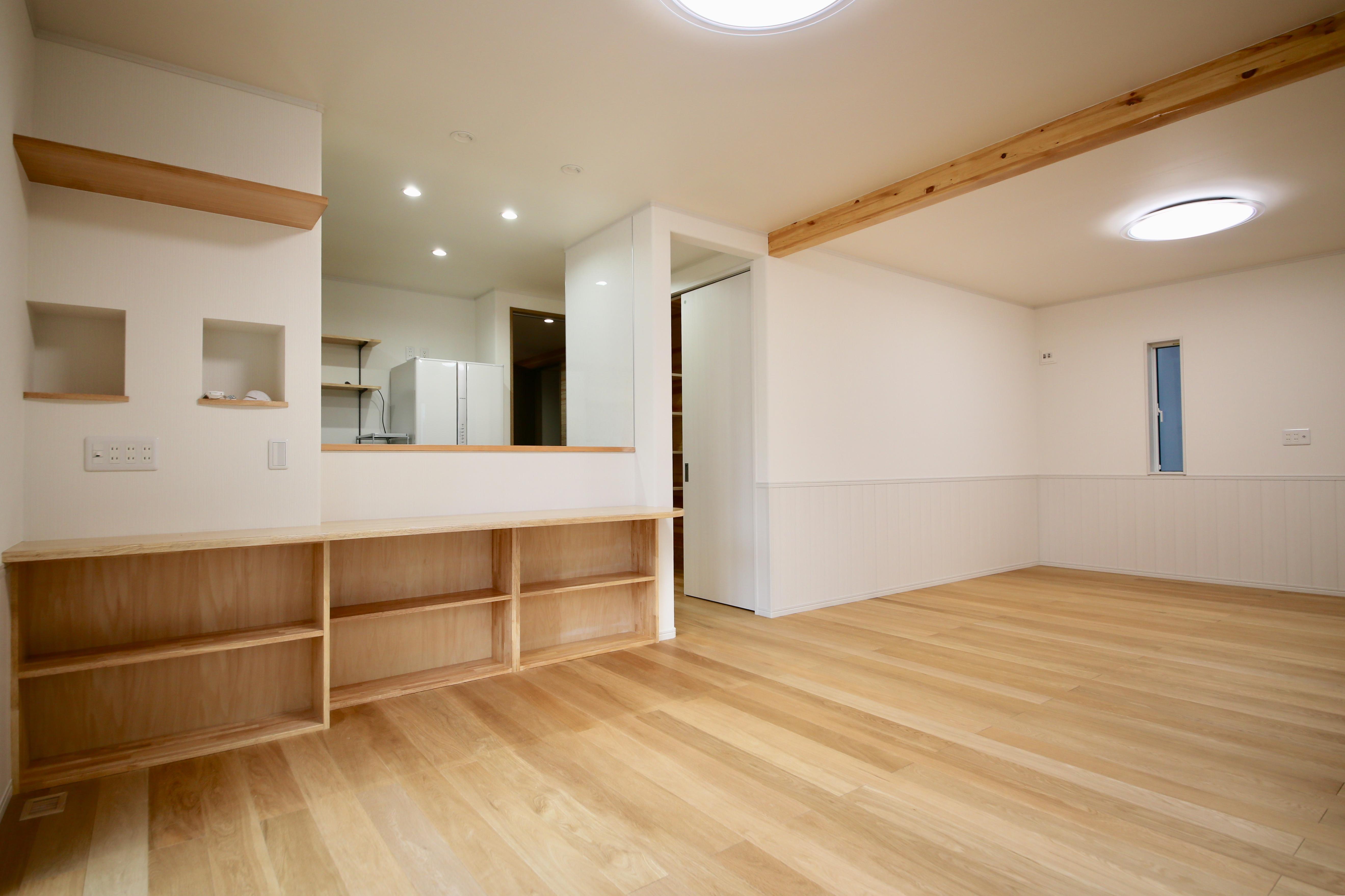 広々としたLDK。床はオーク。造作の棚やカウンター、現しにした梁など随所に木の温もりがあふれる
