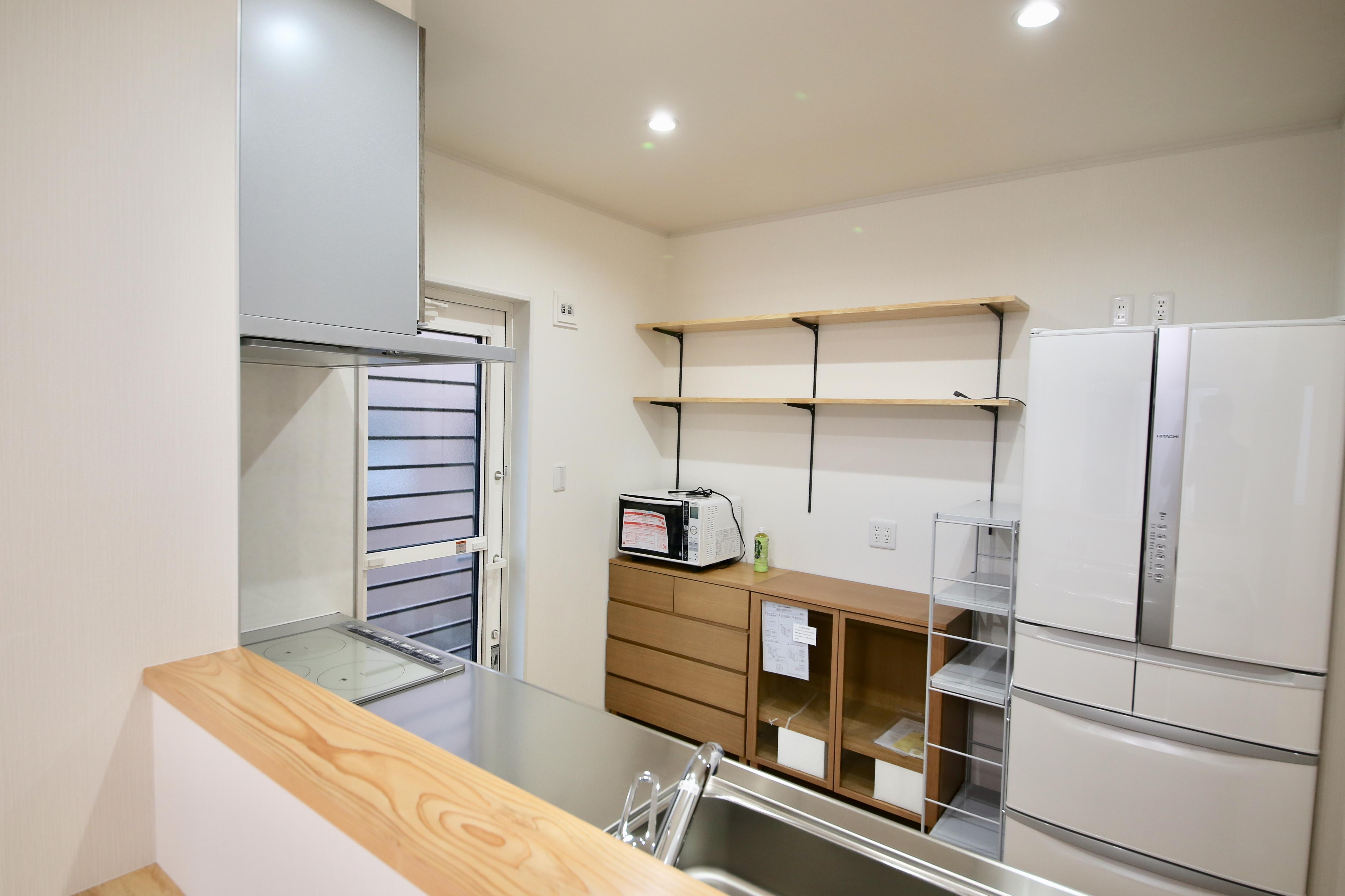キッチン背面には高さを変えられる棚を設置し、十分な収納スペースを設けた。IHヒーターの採用で掃除も簡単に
