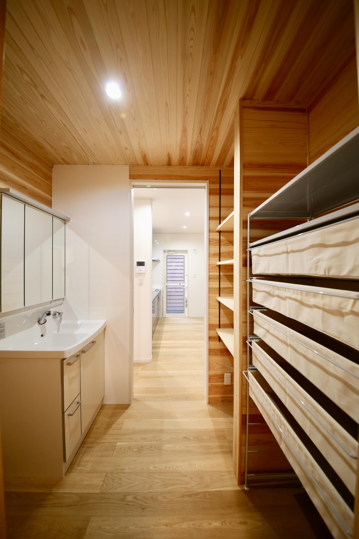 キッチンから洗面・脱衣所までは一直線。移動距離を最小限にして家事の負担を軽減している。脱衣所の壁には湿気に強い杉の無垢板を貼った