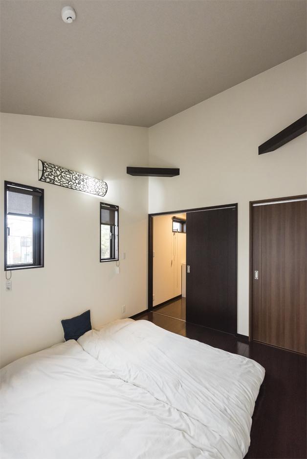 勾配天井になっている寝室は、開放感抜群。高さを活かし設置した梁が素敵だ。ウォークインクローゼットには、衣類や書籍などを収納している